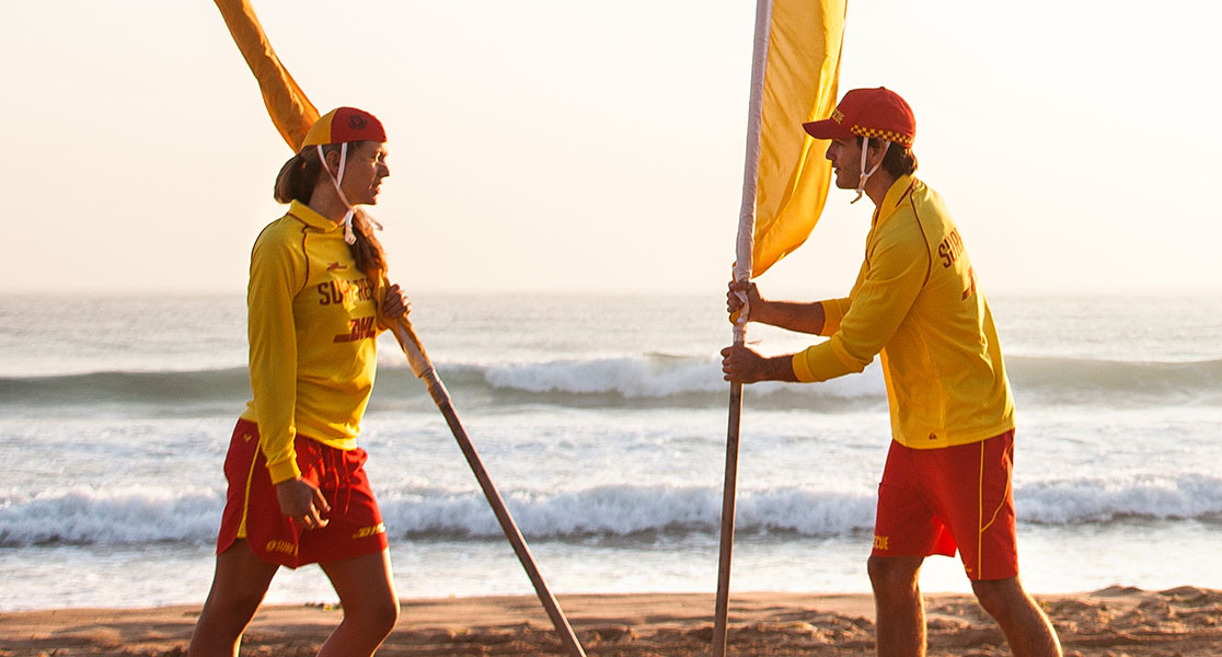 Two surf lifesavers setting up flags