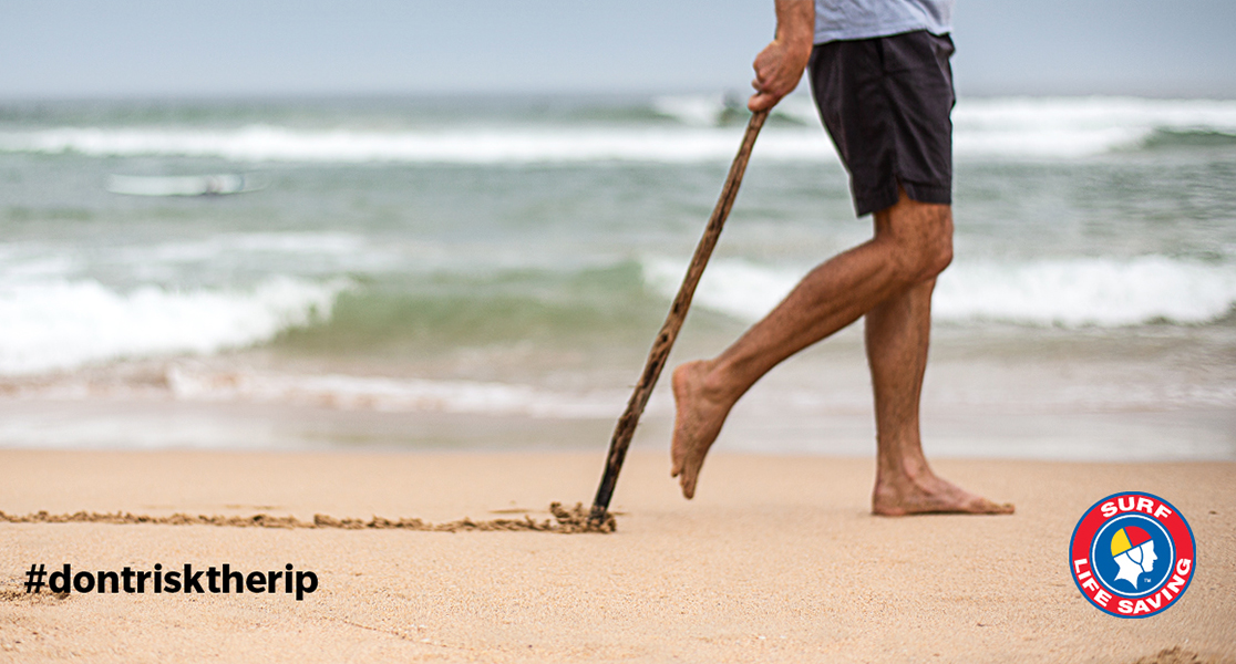 Man drawing a line in the sand with a stick