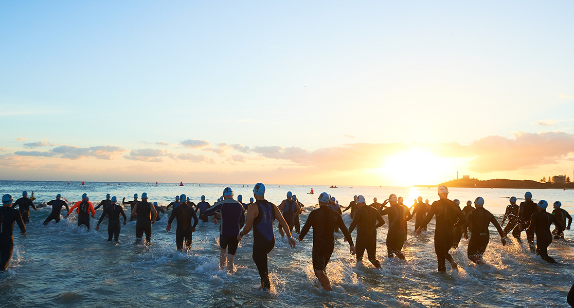 competitors running into the ocean